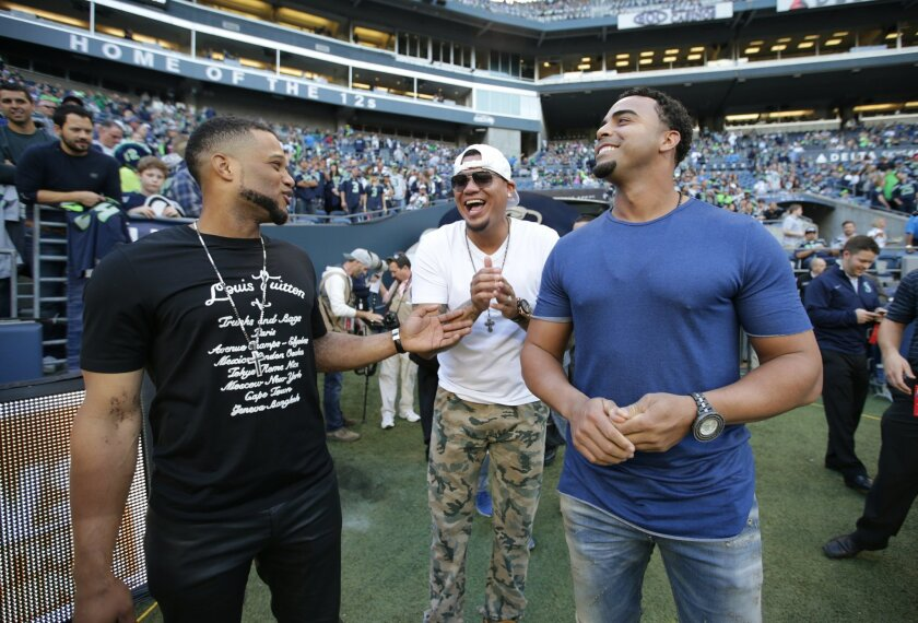 FILE - In this Oct. 5, 2015, file photo, from left, Seattle Mariners baseball players Robinson Cano, Felix Hernandez, and Nelson Cruz visit the Seattle Seahawks sideline before an NFL football game between the Seahawks and the Detroit Lions, in Seattle. All-Star second baseman Robinson Cano is supremely fashion-conscious, and he talks with joy about the collection in his massive closet.(AP Photo/Scott Eklund, File)