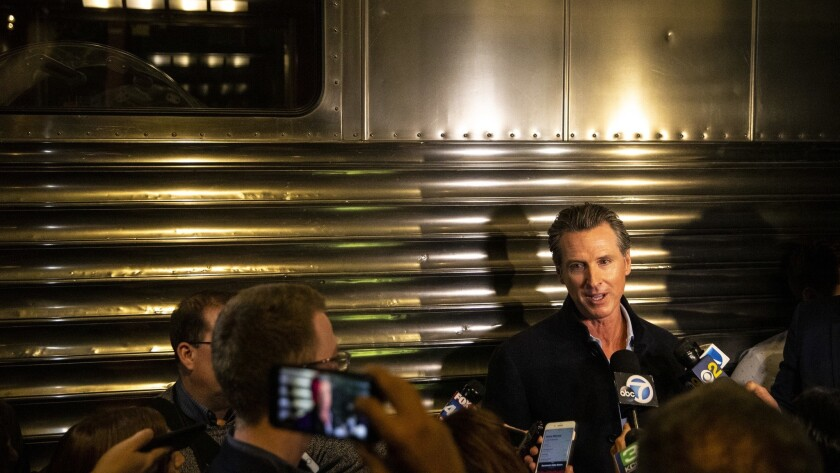 Gavin Newsom speaks with the media after he and his family attend an Inauguration event Sunday at Sacramento's California Railroad Museum.