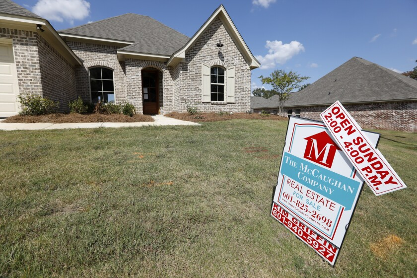 FILE - In this Sept. 25, 2019 file photo, a sign promoting an open house sits atop a realty company's lawn sign in Brandon Miss. Long-term U.S. mortgage rates were mostly steady, Thursday, June 11, 2020, continuing to hover near all-time lows. Mortgage buyer Freddie Mac reports that the average rate on the benchmark 30-year home loan edged up to 3.21% from 3.18% last week. .(AP Photo/Rogelio V. Solis, File)
