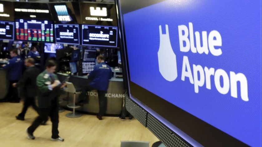 FILE - In this Thursday, Oct. 19, 2017, file photo, the logo for Blue Apron appears on a screen abov