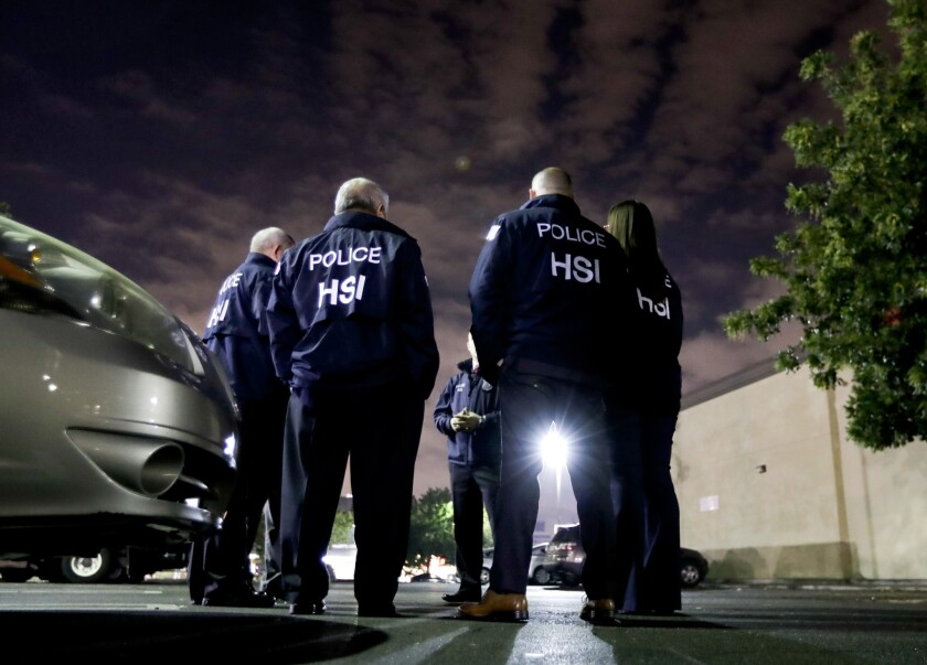 In this Jan. 10, 2018, photo, U.S. Immigration and Customs Enforcement agents gather before serving a employment audit notice at a 7-Eleven convenience store in Los Angeles.