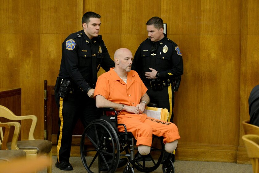 Former New York City police officer Arthur Lomando is wheeled into a courtroom at Bergen County Superior Court for his initial appearance, Thursday, Jan, 28, 2016, in Hackensack N.J., where he pleaded not guilty in the killing of Suzanne Bardzell with a machete-like knife. Lomando, who had both feet amputated, is suing New York City's transit authority for $50 million, claiming he was either jostled, slipped or was hit by falling debris, according to his lawyer. Authorities had said he tried to kill himself by jumping in front of a subway on Oct. 22, hours after allegedly killing Bardzell. (Amy Newman/The Record of Bergen County via AP, Pool)