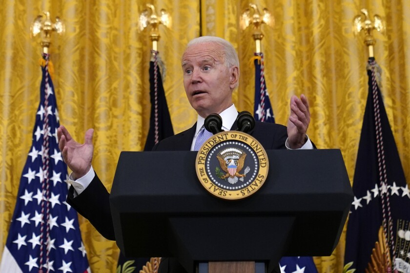 President Biden gestures as he speaks at a lectern with the presidential seal