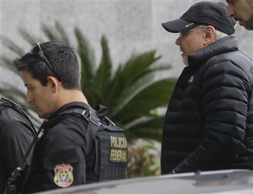 El ex ministro de Finanzas de Brasil Guido Mantega es escoltado por agentes de la Policía Federal al llegar a la sede de la fuerza policiaca en Sao Paulo, el jueves 22 de septiembre de 2016. Mantega fue arrestado el jueves en relación con el extenso escándalo de corrupción en la petrolera estatal Petrobras.