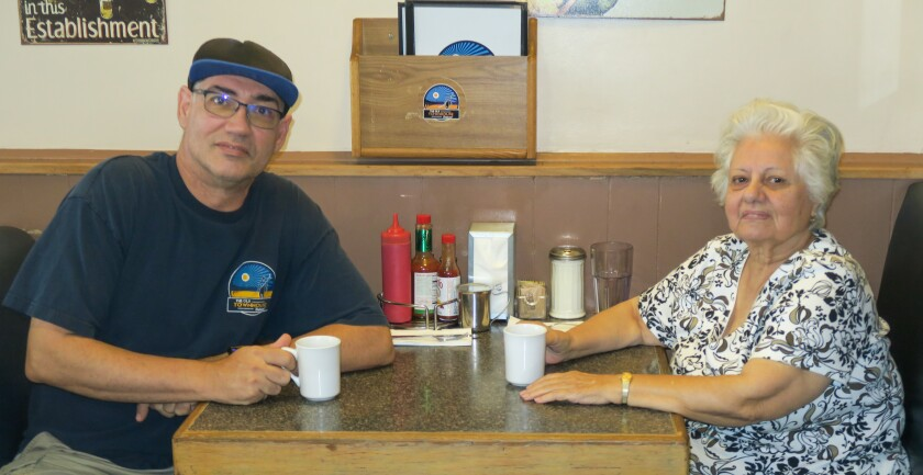 Restaurant owners Ted Caplaneris and his mother Soula take a coffee break in one of the roomy booths.