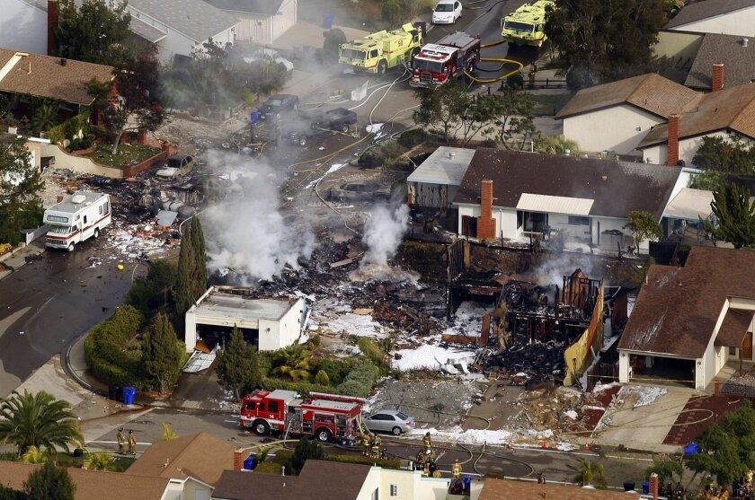 The wreckage of an FA-18 jet headed to MCAS Miramar smolders after it crashed in the University City area of San Diego on Monday, Dec. 8, 2008.