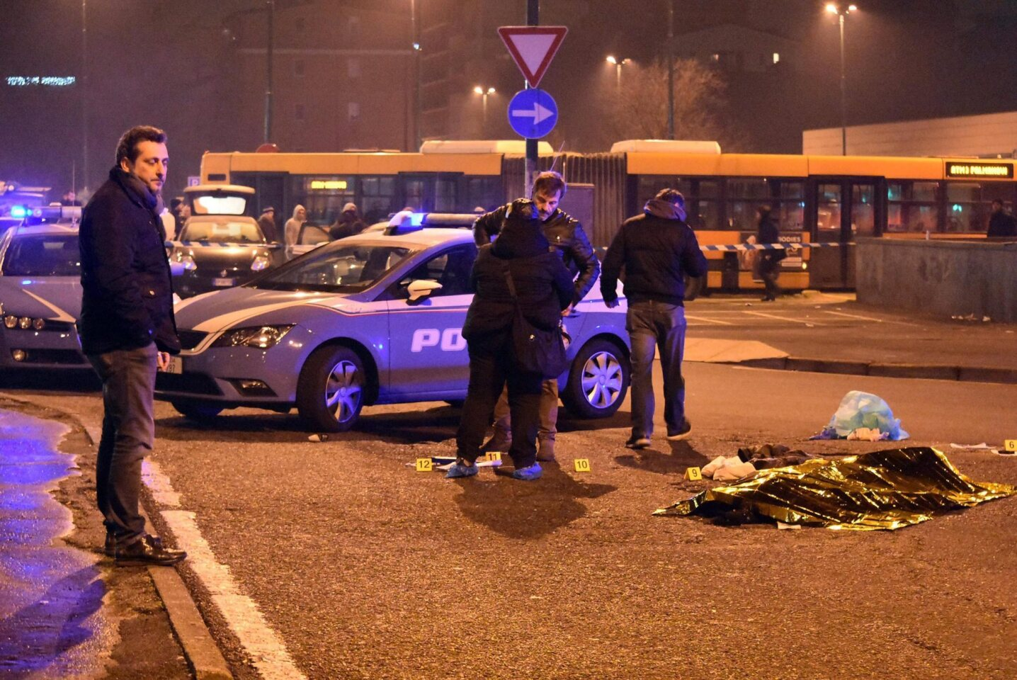 Italian police stand around the body of suspect Anis Amri after a shootout in Milan's Sesto San Giovanni neighborhood early Friday.