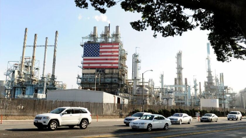 Vehicles drive by the Tesoro petroleum refinery in Carson. A state program meant to reduce pollution by making industries pay for pollution rights isn't working as hoped.