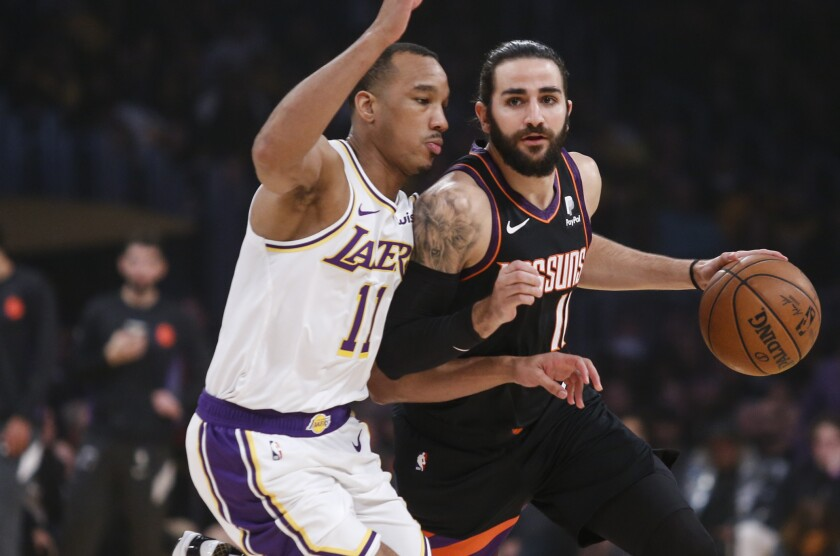 Lakers guard Avery Bradley, left, tries to cut off a drive by Phoenix Suns guard Ricky Rubio.