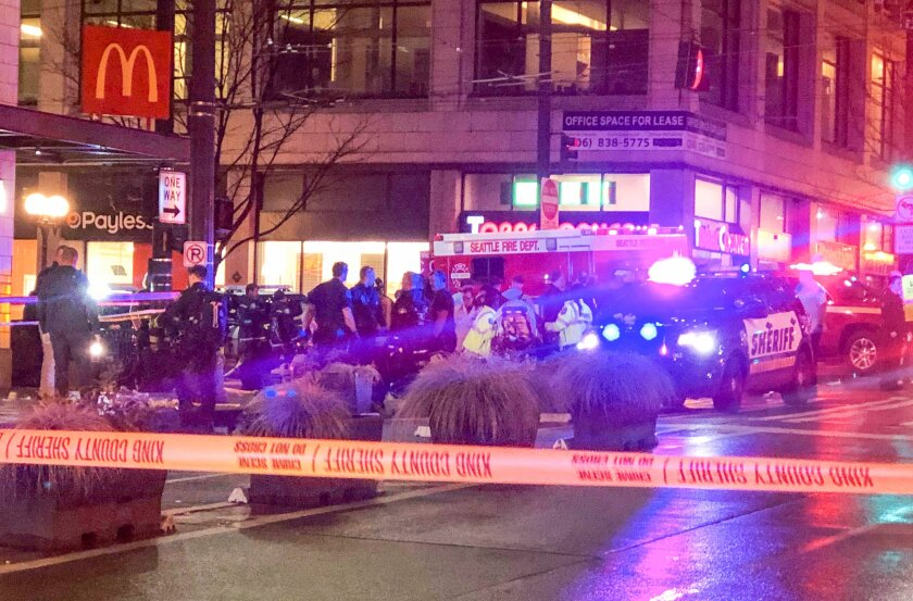 Police investigate the scene of a shooting on Third Avenue and Pine Street in Seattle on Wednesday.