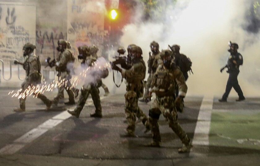 Federal officers fire tear gas at protesters July 17  in Portland, Ore.