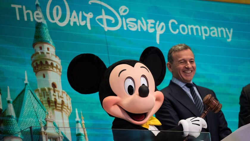 Mickey Mouse and Bob Iger, Walt Disney Co.'s chairman and chief executive, ring the opening bell at the New York Stock Exchange on Nov. 27 to mark Disney's 60th anniversary as a listed company on the NYSE.