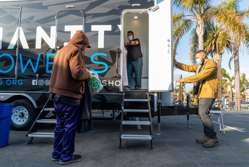 Jordan Verdin holds the door for a homeless man about to step into the Humanity Showers trailer in Oceanside.