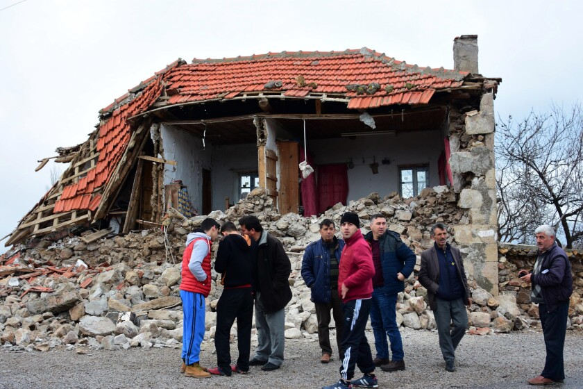 Villagers in front of a damaged house after two quakes, both with preliminary magnitudes of 5.3, jolted Turkey's northern Aegean coast, in Yukarikoy village Canakkale province, Monday, Feb. 6, 2017, damaging dozens of homes in at least five villages and injuring several people.