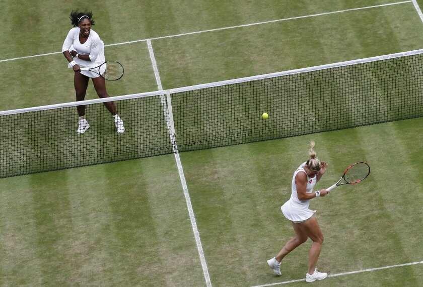 Serena Williams of the U.S, left, returns to Timea Babos of Hungary, right, and Yaroslava Shvedova of Kazahkstan, not pictured, during her women's doubles final with playing partner Venus Williams of the U.S on day thirteen of the Wimbledon Tennis Championships in London, Saturday, July 9, 2016. (A
