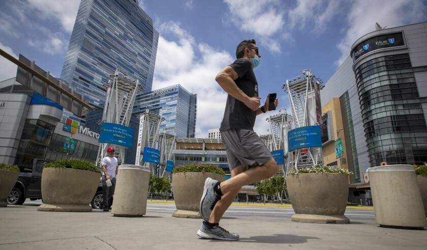 A jogger passes L.A. Live in downtown Los Angeles in mid-June.