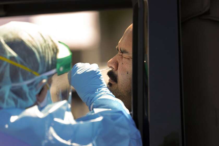 A healthcare worker collects a nasal swab from Victor Guardavo for coronavirus testing in San Bernardino County.