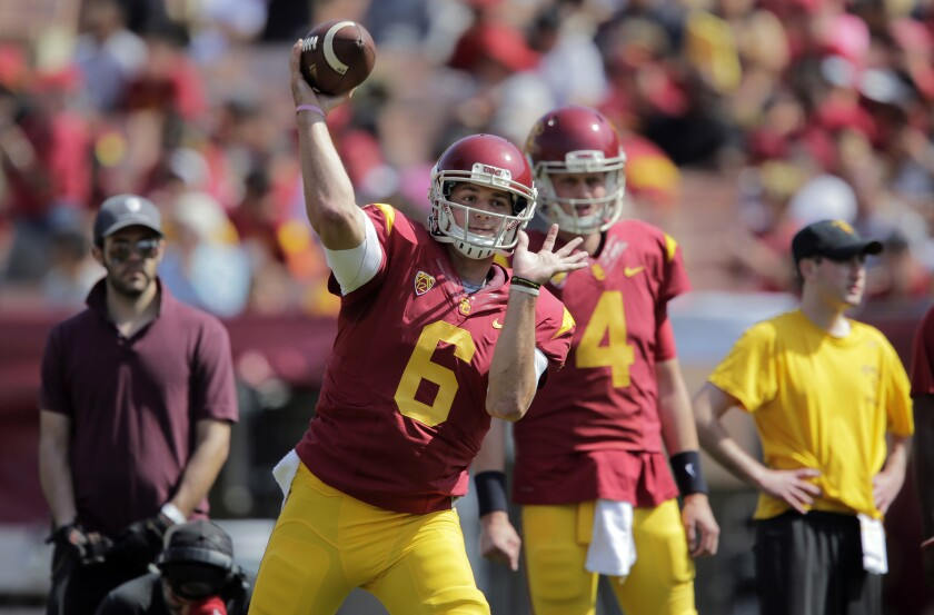 USC quarterback Cody Kessler loosens up alongside Max Browne before the Trojans' annual spring game on Saturday at the Coliseum.