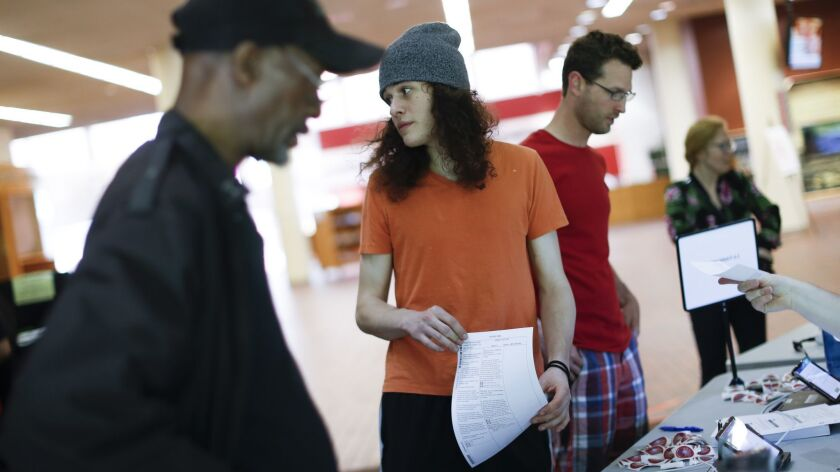 A voter checks in before filling out a ballot at the Cincinnati Public Library precinct on primary e