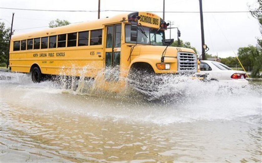 A Guilford County School bus navigates through a partially flooded section of Yanceyville Street near East Cornwallis Drive during its morning travels in Greensboro, N.C., Wednesday, September 30, 2010. (AP Photo/Nelson Kepley, News & Record).