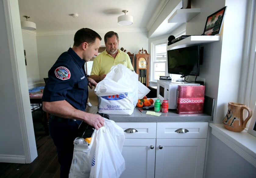Glendale Firefighter-Paramedic Spencer Hammond delivers groceries to 64-year-old Jim Rohrig. The Glendale Fire Department has offered to deliver groceries to the city's vulnerable population who are sheltering in place because of the coronavirus.