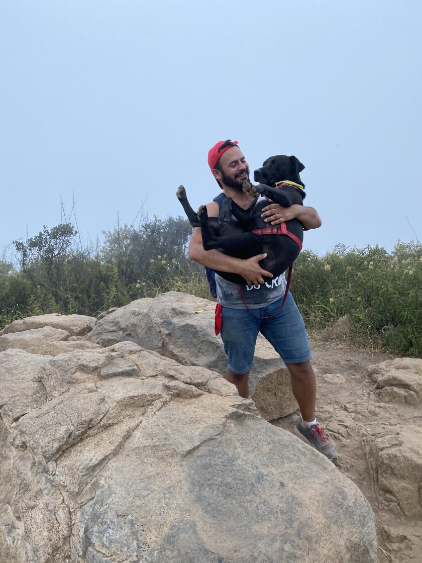 Allan Acevedo, writer and mom's favorite, with his dog, Zeus.