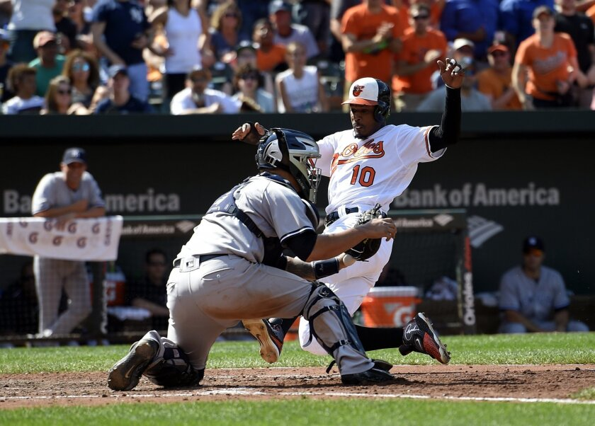 Baltimore Orioles' Adam Jones (10) comes home to score on a double by Pedro Alvarez during the fifth inning of a baseball game against New York Yankees catcher Gary Sanchez, left, Sunday, Sept. 4, 2016, in Baltimore. The Yankees won 5-2. (AP Photo/Nick Wass)