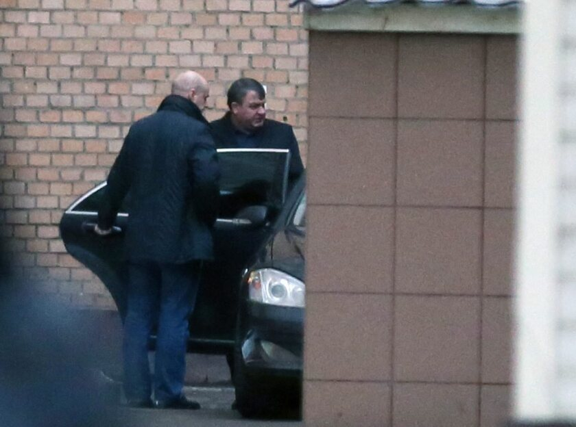 Former Russian Defense Minister Anatoly Serdyukov, right, leaves the Investigative Committee office in Moscow on Friday.