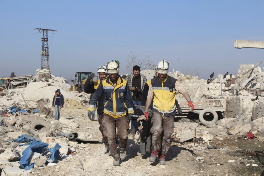Syrian workers carry a victim following airstrikes in Maaret Musreen village on Thursday.