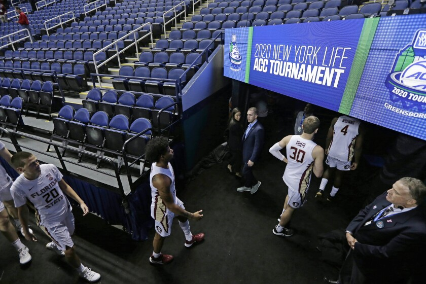 FILE - In this Thursday, March 12, 2020, file photo, Florida State players leave the court after the NCAA college basketball games at the Atlantic Coast Conference tournament in Greensboro, N.C., were cancelled due to the coronavirus. A year after the worldwide coronavirus pandemic stopped all the games in their tracks, the aftershocks are still being felt across every sector. (AP Photo/Gerry Broome, File)