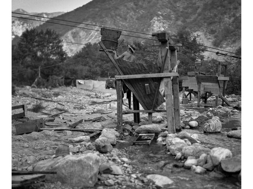 Gold miner Joey Brandt works with a conveyer bucket, a hopper and a sluice box over a stream in San Gabriel Canyon.