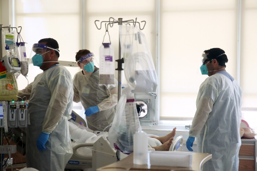 Healthcare workers in protective gear surround a patient in a hospital bed