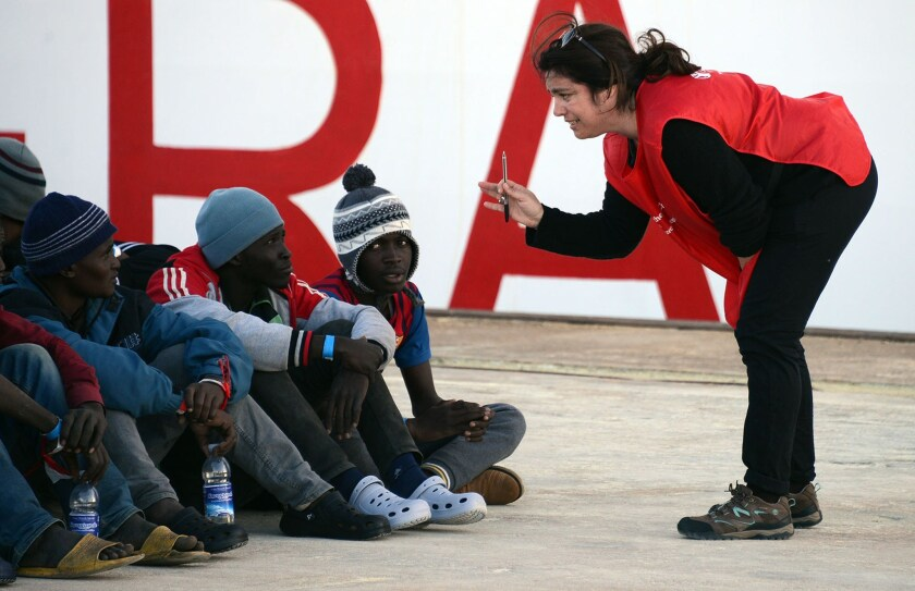 Shipwrecked migrants listen to an Italian Red Cross worker after disembarking from a rescue vessel in the Italian port of Augusta on April 16.