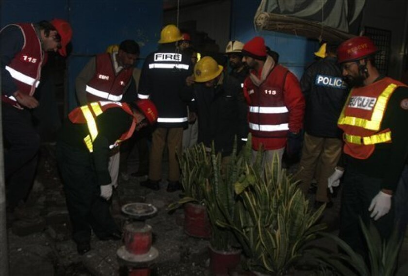 Pakistani firemen and rescue workers at the site of explosions in Lahore, Pakistan Friday, Jan. 9, 2009. Four small bombs exploded outside a theater and near a major government building in an eastern Pakistan city late Friday but there were no casualties, police said. (AP Photo/K.M.Chaudary)