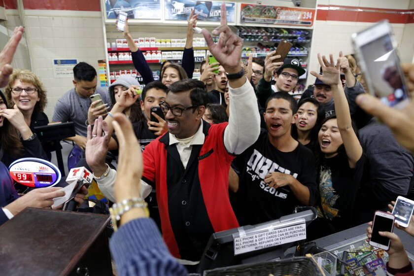 Lottery fans celebrate at the Chino Hills 7-Eleven store where one of the winning tickets in the $1.5-billion Powerball drawing was sold.