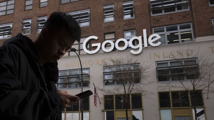 FILE - In this Dec. 17, 2018, file photo, a man using a mobile phone walks past Google offices in Ne