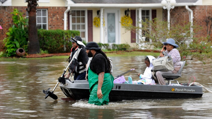Volunteers pull a boat with a woman and young child as they evacuate from their homes on Aug. 13 in Baton Rouge, La.