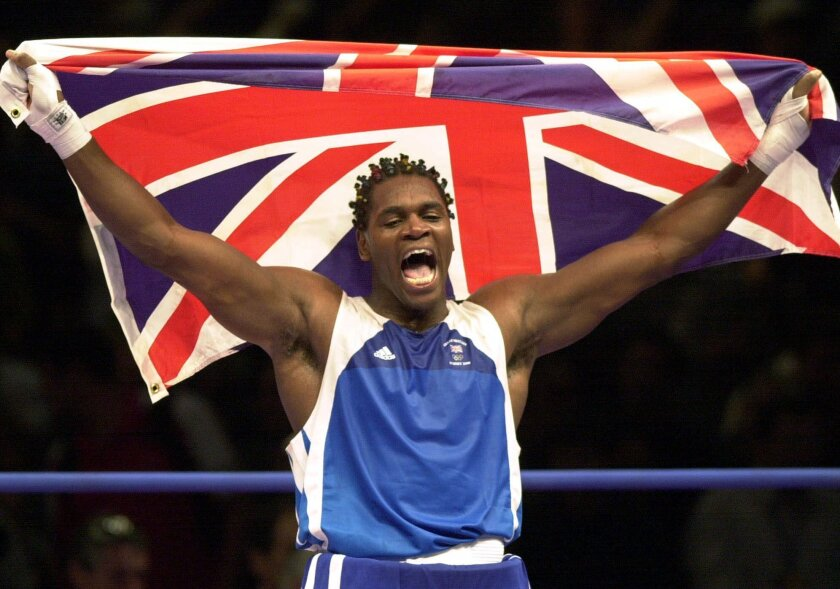 FILE - This is a Sunday Oct. 1, 2000 file photo of Audley Harrison of  Britain celebrates his gold medal victory in the super-heavyweight division in Sydney, Australia. Former Olympic boxing champion Audley Harrison has announced his retirement, saying repeated blows to the head have left him with