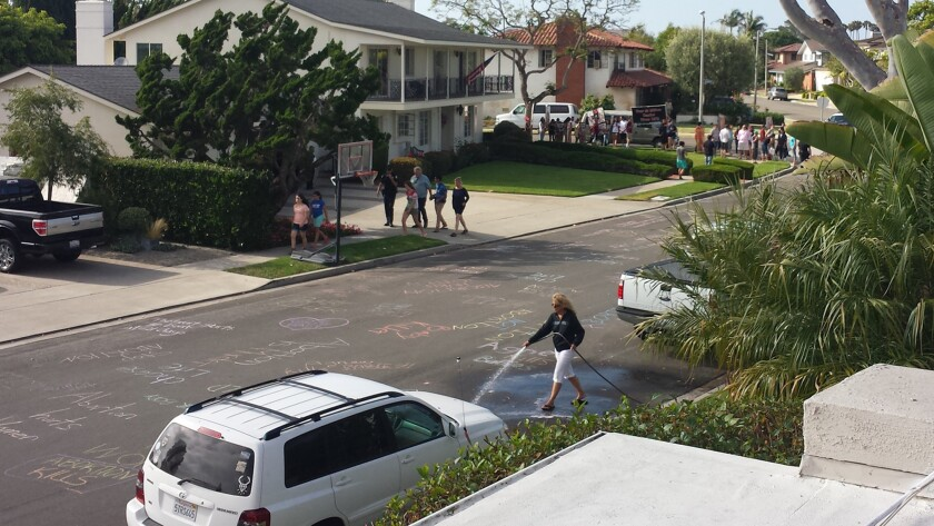 Paula Durnian hoses off anti-abortion messages written in chalk on the street in Newport Beach. Twice in the past week, pro-life protestors allegedly left messages targeting Durnian's neighbor, Dr. Richard Agnew, an OBGYN.