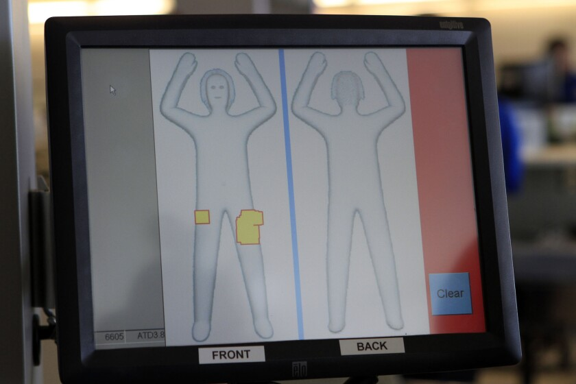 A TSA officer demonstrates the use of full-body scanners at Ontario International Airport. The TSA can now require passengers to go through the scanner even if the passengers asks for a pat-down search instead.