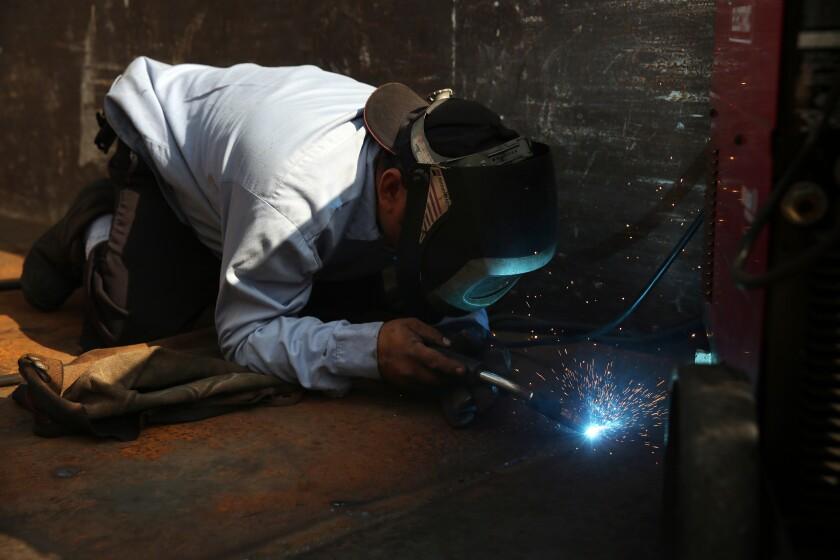 Juan Gabriel Sanchez works on a truck at Western Truck Exchange.