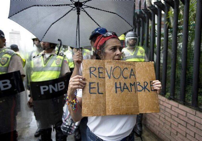 Una mujer sostiene un letrero durante una marcha de protesta de la oposición en Caracas,, la crisis económica ha dejado a los revendedores como los ganadores de la crisis económica.