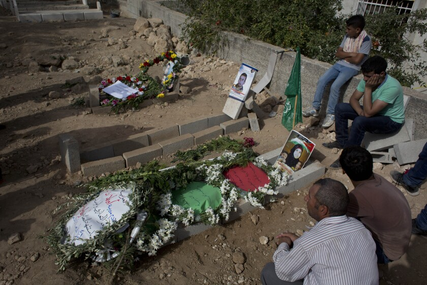 FILE - In this Sept. 7, 2015 file photo, Palestinians mourn at the graves of Riham Dawabsheh, 27, her husband Saed Dawabsheh and their 18-month-old son Ali, in the West Bank village of Duma, near Nablus. On Monday, Sept. 14, 2020, the Lod District Court handed down three life sentences to Jewish extremist Amiram Ben-Uliel convicted in a 2015 arson attack that killed the Palestinian toddler and his parents. (AP Photo/Nasser Nasser, File)