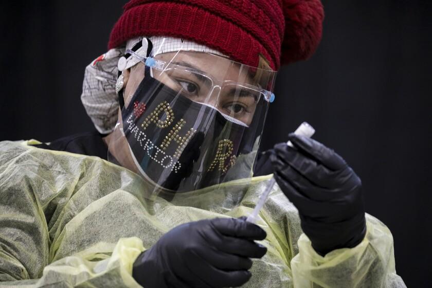 Nurse Crystal Martin prepares a dose of Pfizer-BioNTech COVID-19 vaccine