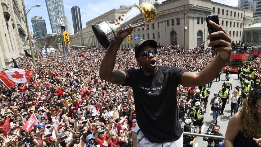 Toronto Raptors forward Kawhi Leonard takes a selfie holding his playoffs MVP trophy during the NBA