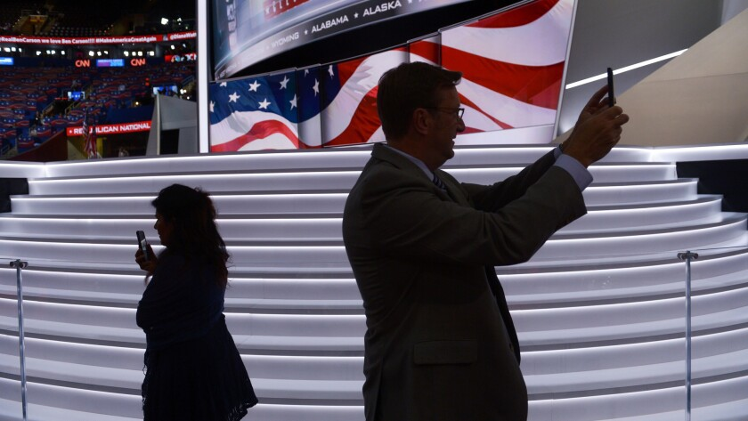 People use their mobile phones as preparations are underway at Quicken Loans Arena for day three of the Republican National Convention in Cleveland, Ohio on July 20, 2016.