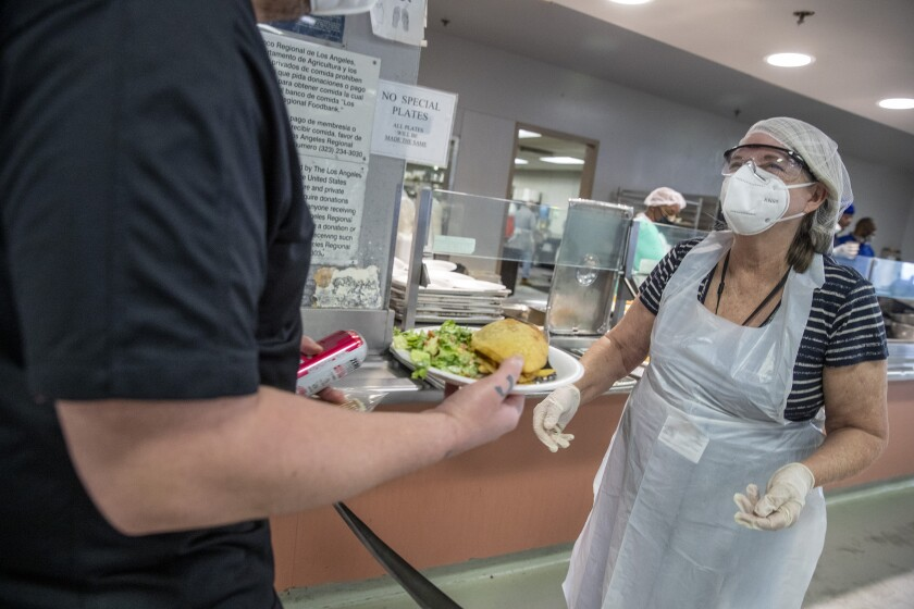 Teacher Jenny Kershner, right, helps serve lunch at the Union Rescue Mission in Los Angeles in July.