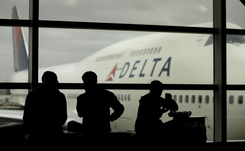 """Delta Air Lines passengers wait for flights in Detroit. The airline has requested trademark protection for the slogan """"The World's Most Trusted Airline."""""""