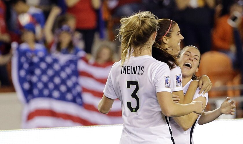 United States' Alex Morgan, center, celebrates her goal with Samantha Mewis (3) and Kelley O'Hara, right, against Trinidad and Tobago during the second half of a CONCACAF Olympic women's soccer qualifying championship semifinal Friday, Feb. 19, 2016, in Houston. The U.S. won 5-0. (AP Photo/David J. Phillip)