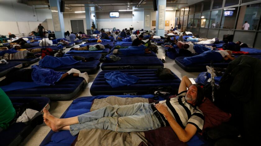 Kurt Kruhlinski, 53, foreground, joins dozens of other homeless men in the day room that is now being used in the evening for emergency bedding at the Union Rescue Mission.